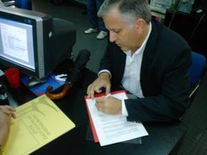 El Lic. Luis Parodi, firmando su presentación en la municipalidad.